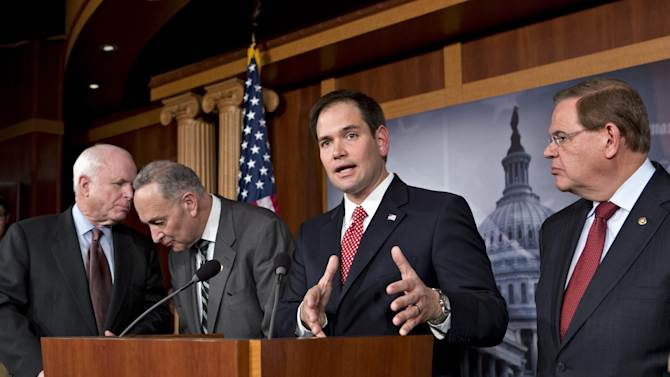 """FILE – In this Jan. 28, 2013, file photo Sen. Marco Rubio, R-Fla., center,speaks at a Capitol Hill news conference with a bipartisan group of leading senators to announce their agreement on the principles of sweeping legislation to rewrite the nation's immigration laws. Eight senators meet in private several times a week, alternating between, from left, Sen. John McCain's, R-Ariz., and Sen. Charles Schumer's, D-N.Y., offices, and in a capital riven by partisanship and gridlock, they are determined to be the exception and actually get something done. This is immigration reform's """" Gang of Eight"""".  At right is Sen. Robert Menendez, D-N.J., The group includes Sen.s Lindsey Graham, R–S.C., Dick Durbin, D-Ill., Jeff Flake, R-Ariz., and Michael Bennet, D-Colo., not shown here. (AP Photo/J. Scott Applewhite)"""