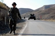 File picture shows Turkish soldiers on patrol on a road near Hakkari. Fighting between Turkish soldiers and Kurdish rebels killed 19 people in the southeast of the country early Sunday, the local governor told the Anatolia news agency
