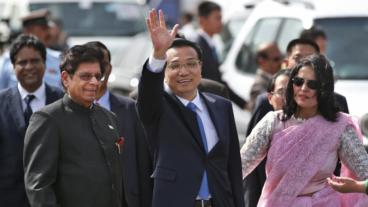 Chinese Premiere Li Keqiang waves as he is received by Indian Junior Minister for External Affairs, E. Ahamed, left, after he arrives in New Delhi, India, Sunday, May 19, 2013. Just weeks after a tense border standoff, China's new premier arrived in India on Sunday for his first foreign trip as the neighboring giants look to speed up efforts to settle a decades-old boundary dispute and boost economic ties. A woman at right is a protocol officer. (AP Photo/ Saurabh Das)