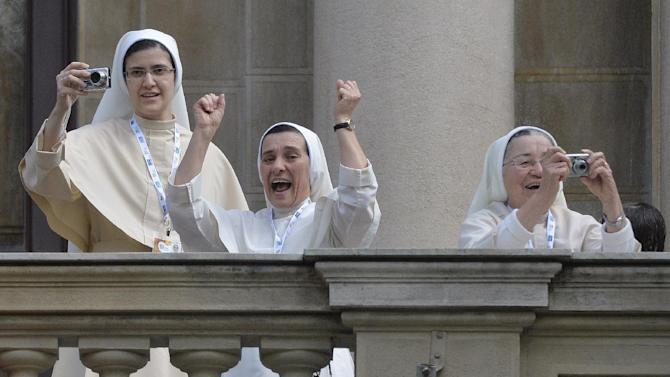 Nuns celebrate and take pictures as Pope Francis arrives to give Angelus noon prayer as they stand on a balcony at Sao Joaquim Palace in Rio de Janeiro, Brazil, Friday, July 26, 2013. Pope Francis is on the fifth day of his trip to Brazil where he will attend the 2013 World Youth Day in Rio. (AP Photo/Luca Zennaro, Pool)