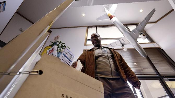 With a model 757 over his shoulder, Ernest Griffin drops his ballot at the headquarters of the union for Boeing Co.'s engineers and technical workers, Tuesday, Feb. 19, 2013, in Tukwila, Wash. Members of the Society of Professional Engineering Employees in Aerospace (SPEEA) are voting on a contract offer from the company and whether to authorize a strike. The union represents 23,000 employees, mostly in the Puget Sound region. Negotiations began in April and union members rejected one offer in October. The previous contract expired in November. (AP Photo/Elaine Thompson)