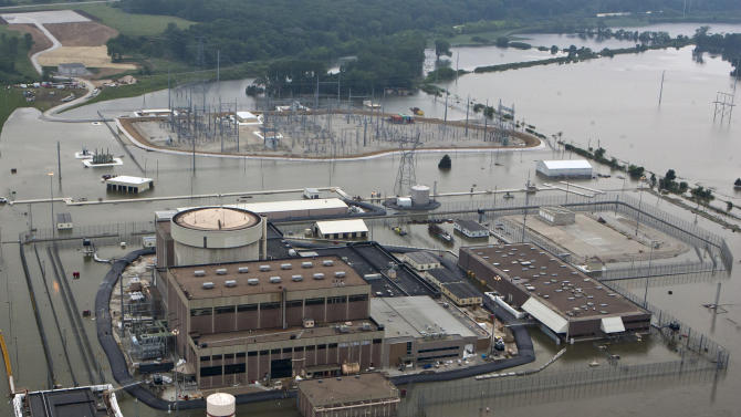 FILE - In this July 14, 2011 file photo, the Fort Calhoun nuclear power plant is surrounded by floodwaters from the Missouri River, in Fort Calhoun, Neb. The troubled nuclear power plant is inching closer to restarting as the Nuclear Regulatory Commission issues a checklist this week outlining everything that must be done before the plant restarts. But it's still not clear exactly when that will happen because federal regulators say there is no timeline. (AP Photo/Nati Harnik, File)