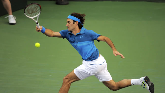 Roger Federer, of Switzerland, returns a shot to Rafael Nadal, of Spain, during a semifinal at the BNP Paribas Open tennis tournament, Saturday, March 17, 2012, in Indian Wells, Calif. (AP Photo/Mark J. Terrill)