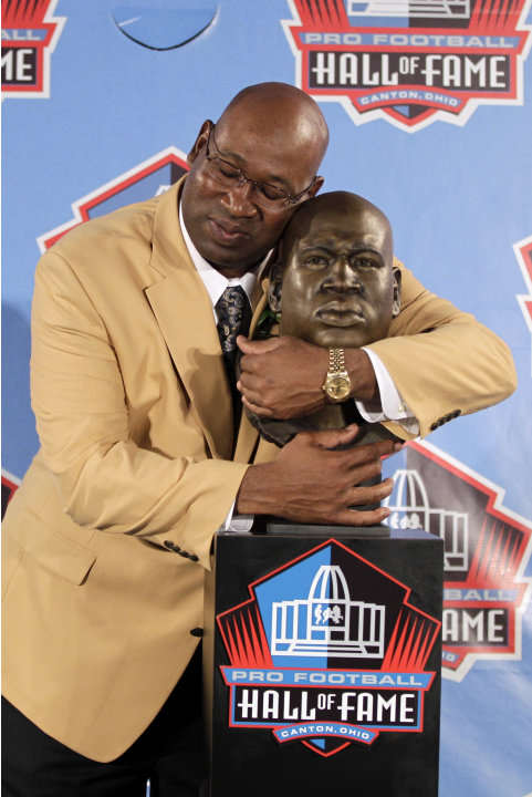 Former NFL player Cortez Kennedy poses with a bust of himself during the induction ceremony at the Pro Football Hall of Fame, Saturday, Aug. 4, 2012, in Canton, Ohio. (AP Photo/Gene J. Puskar)