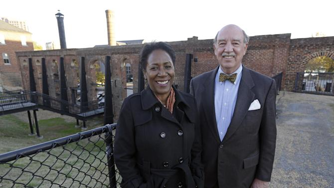 Christy Coleman, left, director of the American Civil War Center at Tredegar Iron Works, left, and Waite Rawls of the Museum of the Confederacy, pose in front of the ruins of the old Tredegar Iron Works in Richmond, Va., Wednesday, Nov. 13, 2013. (AP Photo/Steve Helber)