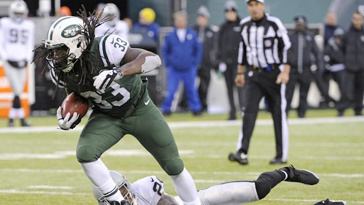 In this Dec. 8, 2013 file photo, New York Jets running back Chris Ivory (33) breaks away from Oakland Raiders safety Charles Woodson during the second half of an NFL football game, in East Rutherford, N.J. Ivory's carries the ball like a man possessed