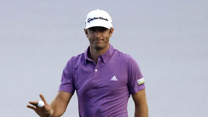 Dustin Johnson waves after making a putt on the 13th hole during the first round at the Tournament of Champions PGA golf tournament, Monday, Jan. 7, 2013, in Kapalua, Hawaii. Play was to have started three days earlier, but was delayed because of rain and high winds. (AP Photo/Elaine Thompson)