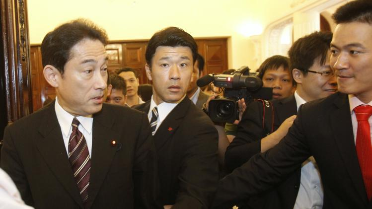 Kishida enters a meeting room at the Government Guesthouse in Hanoi