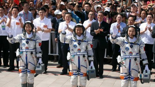 Mission commander Jing Haipeng (R) and fellow astronauts Liu Wang (C) and Liu Yang wave to the crowd