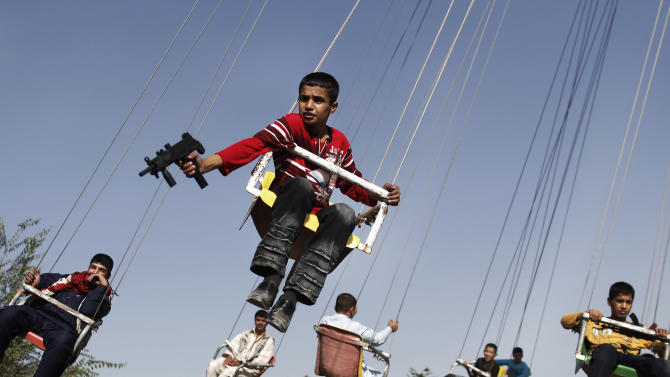 FILE - The Sept. 20, 2009 file photo shows an Afghan boy holding a toy gun as he enjoys a ride with others on a merry-go-round to celebrate the Eid al-Fitr festival, in Kabul, Afghanistan. Eid al-Fitr festival marks the end of the Muslim fasting month of Ramadan. The photo is part of the exhibition of AP photographer Anja Niedringhaus 'Anja Niedringhaus At War' which runs from Sept. 10 through Dec. 4, 2011 in the C/O Berlin. (AP Photo/Anja Niedringhaus, file)