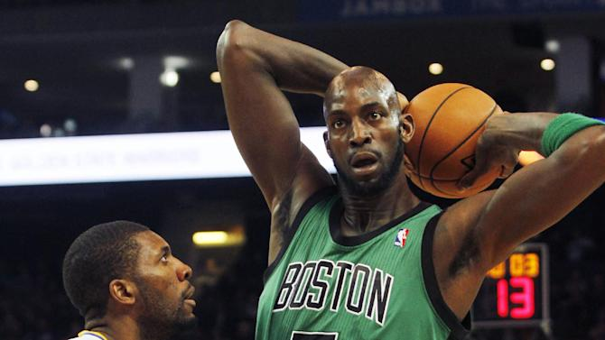 Boston Celtics' Kevin Garnett (5) looks to pass as Golden State Warriors' Festus Ezeli defends during the first half of an NBA basketball game in Oakland, Calif., Saturday, Dec. 29, 2012. (AP Photo/George Nikitin)