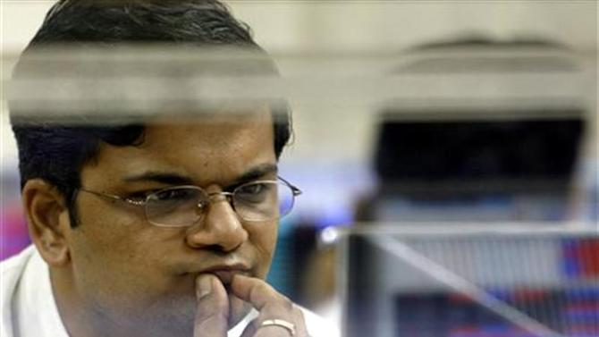 A stockbroker looks at stock index numbers on his computer screen at a brokerage firm in Mumbai
