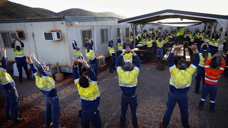 Workers at Fortescue Solomon iron ore mine perform stretching exercises in the Valley of the Kings