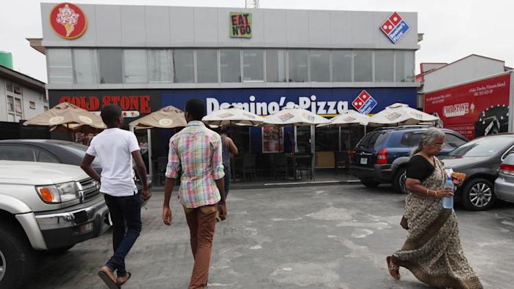 In this photo taken Sunday, Feb. 10, 2013 customers pass restaurants in Lagos, Nigeria. As Nigeria's middle class grows along with the appetite for foreign brands in Africa's most populous nation, more foreign restaurants and lifestyle companies are entering the country. And the draw on Nigerians' new discretionary spending has also put new expectations on providing quality service in a nation where many have grown accustomed to expecting very little. ( AP Photo/Sunday Alamba)