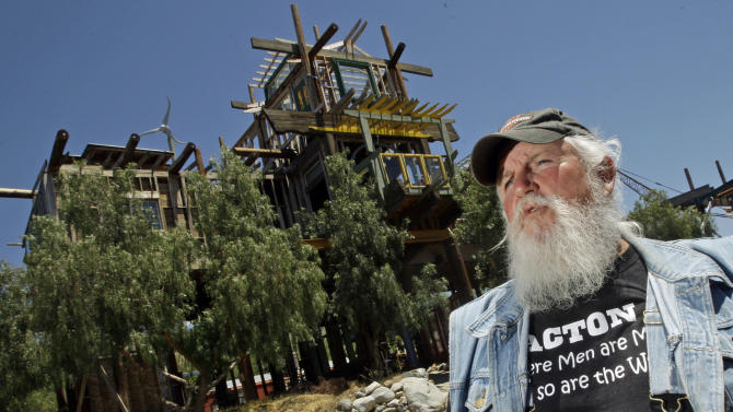 FILE - Kim Fahey is seen with his Phonehenge monument at his home in Acton, Calif., in a mountainous arid area north of Los Angeles, in this June 14, 2011 file photo. Alan Kimble Fahey was sentenced to nearly 18 months in jail because he failed to pay for its demolition, Los Angeles County prosecutors said Friday Dec. 21, 2012.  (AP Photo/Reed Saxon, File)
