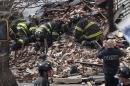 New York City firefighters dig through rubble of a building explosion and collapse in the Harlem section of New York