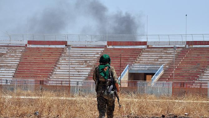 A member of the Kurdish People's Protection Units in a damaged stadium on July 26, 2015 in the Al-Nashwa neighbourhood of the Syrian province of Hasakeh during clashes with Islamic State group jihadists