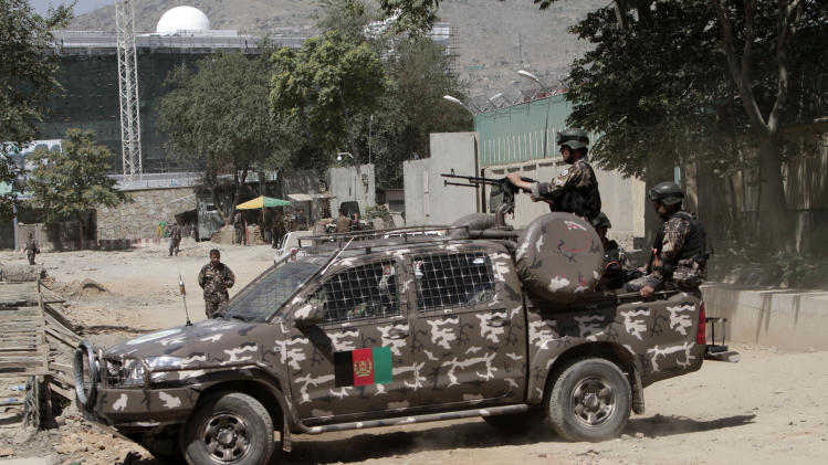 Afghan security forces block a road near the entrance gate of the presidential palace in Kabul, Afghanistan Tuesday, June 25, 2013. Suicide attackers blew up a car bomb and battled security forces outside the presidential palace Tuesday after infiltrating one of the most secure areas of the capital. The Taliban claimed responsibility for the attack, which came as reporters were gathering for a news event on Afghan youth at which President Hamid Karzai was expected to talk about ongoing efforts to open peace talks with the militant group. (AP photo/Rahmat Gul)