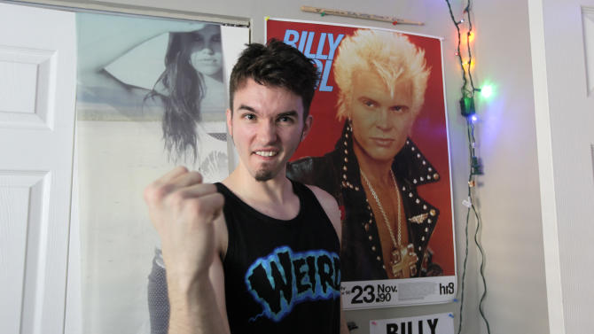 Michael Henrichsen poses for a photo, Sept. 19, 2012 in his bedroom at his home in Seattle next to a poster of rock star Billy Idol. Henrichsen created a website and enlisted friends and celebrities around the world in a two-year effort to convince Idol to come play a concert on Oct. 26, 2012 at a Seattle music venue to raise money for charity and celebrate Henrichsen's birthday. (AP Photo/Ted S. Warren)