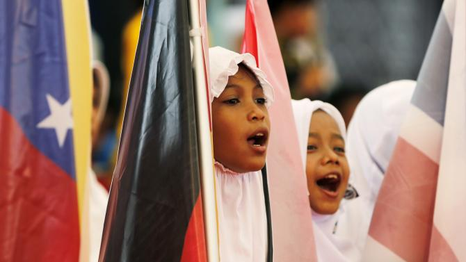 An Acehnese child sings while holding a flag during a ceremony to commemorate the 10th anniversary of the 2004 tsunami in Banda Aceh
