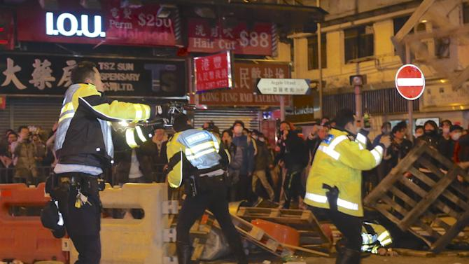 A policeman points his pistol during a clash at Mongkok district in Hong Kong