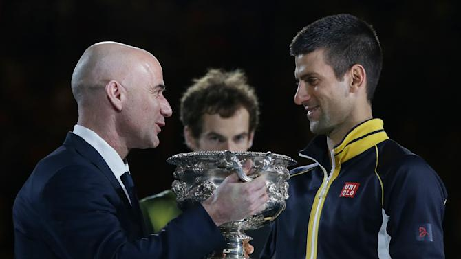 Serbia's Novak Djokovic, right, is presented with the trophy by former Australian Open champion Andre Agassi after defeating Britain's Andy Murray, center, in the men's final at the Australian Open tennis championship in Melbourne, Australia, Sunday, Jan. 27, 2013. (AP Photo/Aaron Favila)
