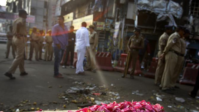 Flowers are placed in memory of those killed, at one of the two bomb blast sites, in Hyderabad, India, Friday, Feb. 22, 2013. A day after two bicycle bombs killed more than a dozen people and wounded more than 100, investigators into India's worst bombing in more than a year searched Friday for possible links to anger over the execution of a Muslim militant. (AP Photo/Aijaz Rahi)