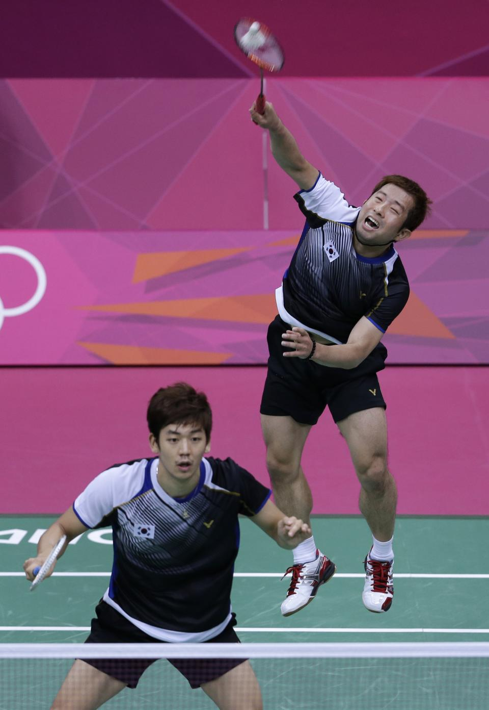 South Korea's Chung Jae-sung, right, and Lee Yong-dae, play against Denmark's Mathias Boe and Carsten Mogensen, unseen, at a men's doubles badminton semifinal match of the 2012 Summer Olympics, Saturday, Aug. 4, 2012, in London. (AP Photo/Saurabh Das)