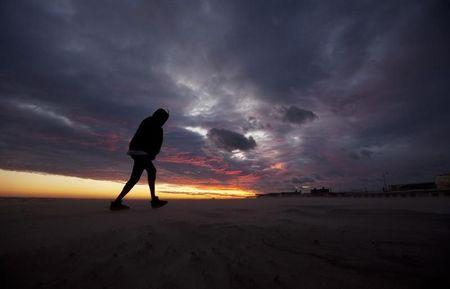 A woman walks off the Long Beach Park beach as the sun sets and the sky clears from Hurricane Irene in Long Beach