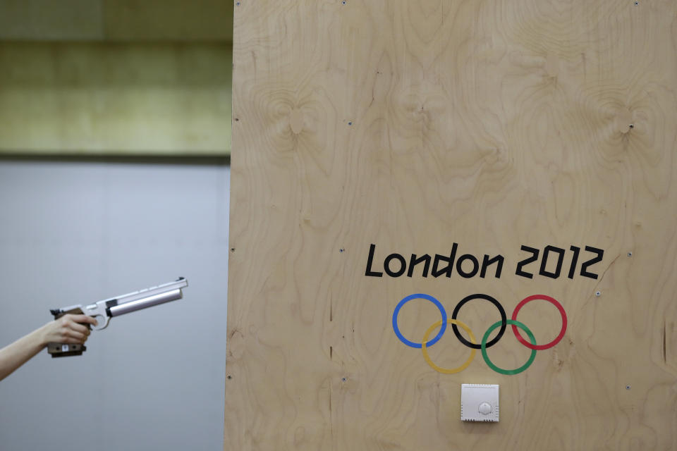 An athlete practices her stance off to the side of the training area for the 10-meter pistol, at the Royal Artillery Barracks ahead of the start of the 2012 Summer Olympics, Thursday, July 26, 2012, in London. (AP Photo/Rebecca Blackwell)