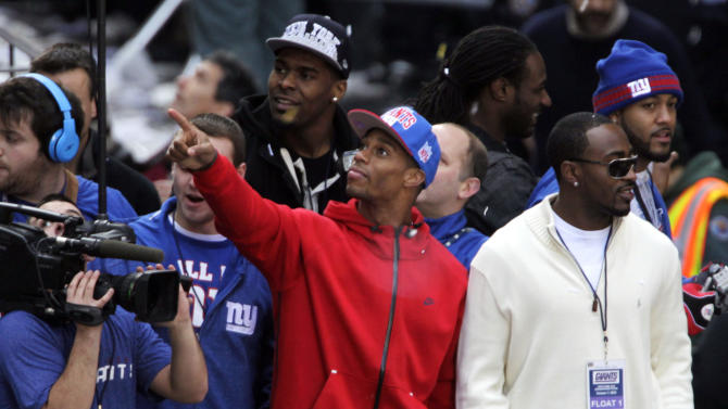 New York Giants' Victor Cruz, center, points to fans during the team's NFL football Super Bowl parade in New York, Tuesday, Feb. 7, 2012. The Giants returned from their Super Bowl win to a celebration the likes that only New York can throw: a ticker-tape parade in the Canyon of Heroes on Broadway, where the city has honored stars for almost a century.(AP Photo/Seth Wenig)
