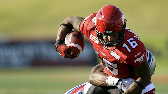 Calgary Stampeders' McDaniel is tackled by Montreal Alouettes' Parker during their CFL football game in Calgary