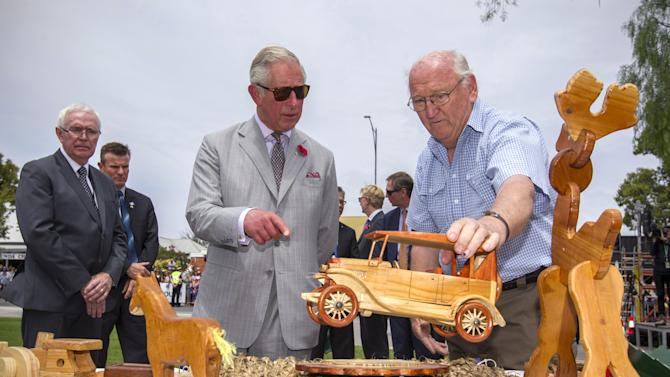Britain's Prince Charles looks at wooden toys made by the local 'Men's Shed' collective in the town of Tanunda