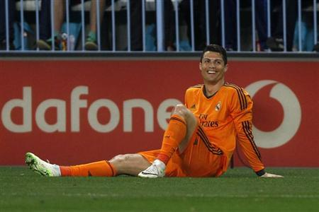 Real Madrid's Cristiano Ronaldo smiles after falling on the pitch during their Spanish First Division soccer match against Malaga at La Rosaleda stadium in Malaga, southern Spain March 15, 2014. REUTERS/Jon Nazca