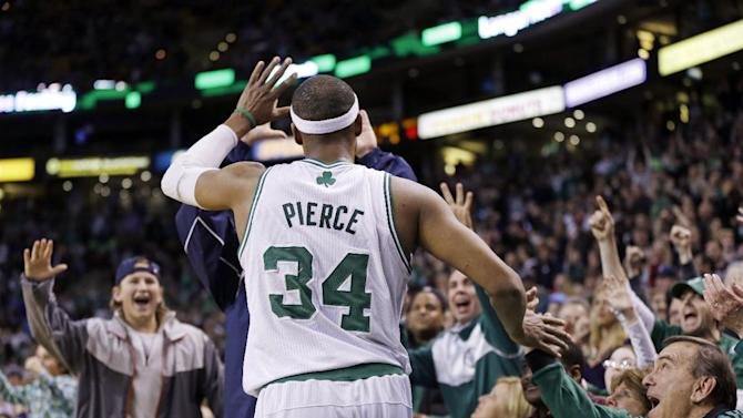 Boston Celtics forward Paul Pierce (34) receives high-fives from courtside fans near the end of the second overtime in an NBA basketball game against the Denver Nuggets in Boston, Sunday, Feb. 10, 2013. The Celtics won 118-114 in triple-overtime. (AP Photo/Elise Amendola)