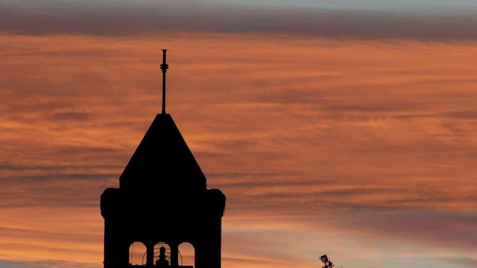 The sunsets over a church in the Australian capital Canberra venue for the Cricket World Cup Pool B match between South Africa and Ireland, in Australia, Tuesday, March 3, 2015. (AP Photo/Rob Griffith)