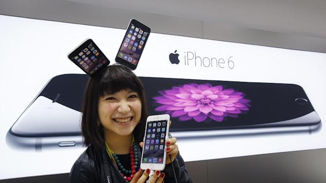 A customer poses for photographers during a ceremony to mark the first day of sales of the new Apple iPhone 6 and 6 Plus at a store  in Tokyo Friday, Sept.  19, 2014. (AP Photo/Shizuo Kambayashi)