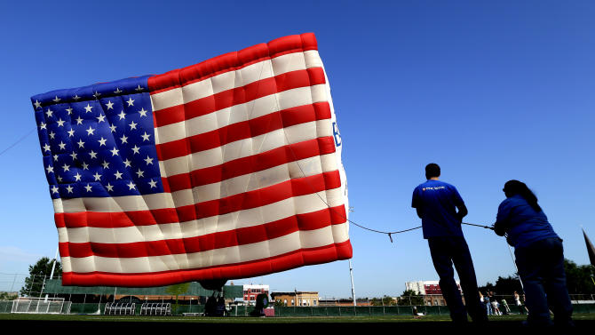 Javier Fernandez, left, and Deanna Wetmore hold a rope as they help a crew flying a hot air balloon draped with the colors of the U.S. flag at Stevens Institute of Technology, Tuesday, July 3, 2012, in Hoboken, N.J. The balloon, which is part of the Quick Chek New Jersey Festival of Ballooning held at the end of of July at Solberg Airport in Readington, N.J., flew in honor of the Fourth of July holiday. (AP Photo/Julio Cortez)
