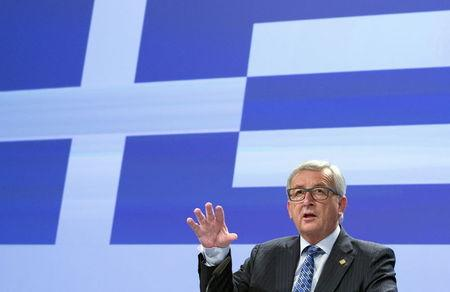 European Commission President Jean-Claude Juncker gives a statement while standing in front a giant Greek flag projected in the press room at the EU commission headquarters in Brussels