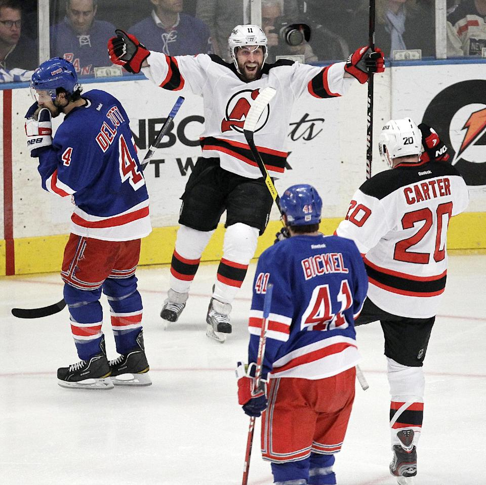 New Jersey Devils' Stephen Gionta, top center, celebrates with Ryan Carter (20) after scoring a goal against the New York Rangers during the first period of Game 5 of an NHL hockey Stanley Cup Eastern Conference final playoff series, Wednesday, May 23, 2012, in New York. (AP Photo/Julio Cortez)