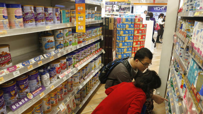 A couple looks at baby formula at a shop in Hong Kong Friday, Feb. 1, 2013. Hong Kong announced measures Friday to curb the amount of baby formula that mainland Chinese visitors are buying as anger grows at shortages in the city's stores. Chief among the measures is a plan to change the law to restrict the amount of baby formula that individuals can take out of the city. Food and Health Secretary Ko Wing-man said legislation would be amended to prohibit taking more than 1.8 kilograms (4 pounds) of formula past Hong Kong's borders. The amount is equal to two cans of formula. (AP Photo/Vincent Yu)