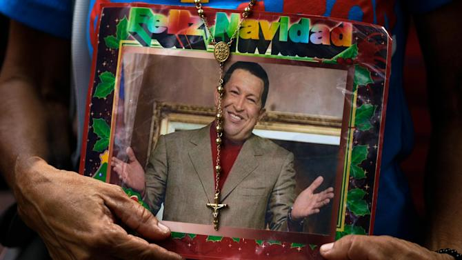"""A supporter of Venezuela's President Hugo Chavez holds a picture of him decorated with a rosary and the words in Spanish """"Merry Christmas"""" outside the National Assembly in Caracas, Venezuela, Saturday, Jan. 5, 2013. Venezuelan lawmakers are meeting Saturday to select a new president of the National Assembly in a session that could give clues to the future of the country amid uncertainty about ailing Chavez. Just five days remain until Chavez's scheduled inauguration on Thursday and officials are suggesting the swearing-in could be delayed. (AP Photo/Fernando Llano)"""