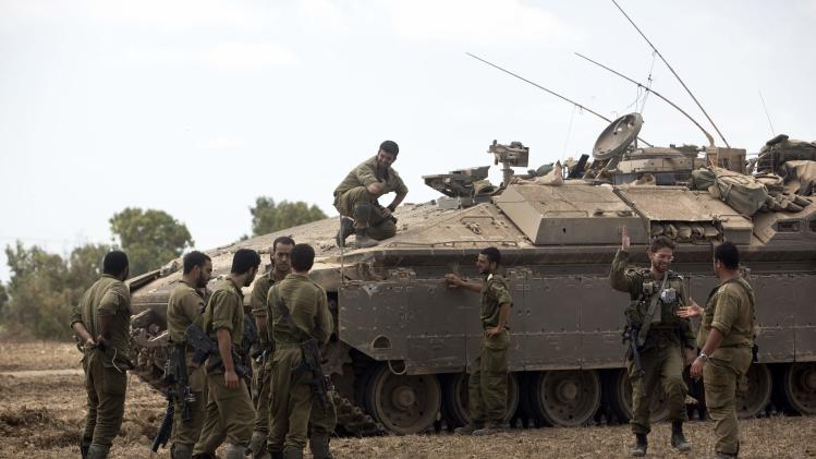 Israeli soldiers meet after ending their duty inside the Gaza Strip, on the Israeli side of the border