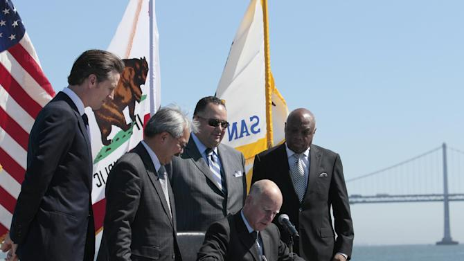 California Gov. Jerry Brown (seated) signs AB 664, a bill to finance improvements the Port of San Francisco needs to host the 2013 America's Cup yacht race, at a news conference in San Francisco, Friday, Sept. 23, 2011. From left to right (standing), California Lt. Gov. Gavin Newsom, San Francisco Mayor Ed Lee, Assembly speaker John Perez and former San Francisco Mayor Willie Brown watch the signing. (AP Photo/Jeff Chiu)