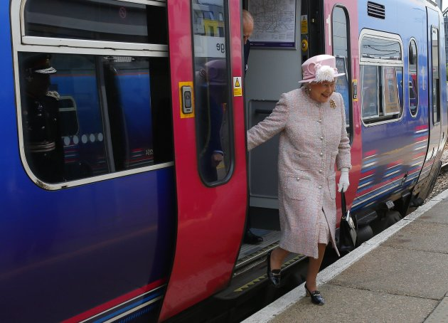 Britain's Queen Elizabeth steps off a train as she arrives for a visit to Cambridge