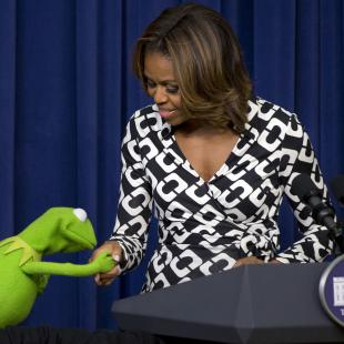 "Kermit the Frog kisses the hand of first lady Michelle Obama, during an event for children in military families in the South Court Auditorium of the Eisenhower Executive Office Building on the White House complex, Wednesday, March 12, 2014, before a screening of Disney's ""Muppets Most Wanted"" movie as part of the Joining Forces initiative. (AP Photo/Jacquelyn Martin)"