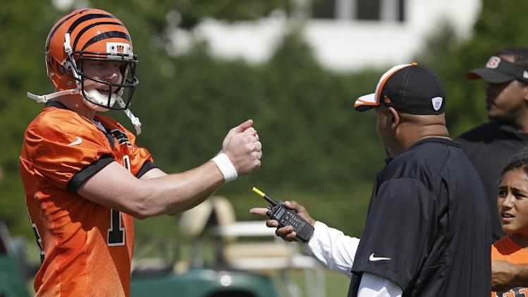 Cincinnati Bengals quarterback Andy Dalton, left, talks with offensive coordinator Hue Jackson, right, during the NFL football team's first practice at training camp, Thursday, July 24, 2014, in Cincinnati. (AP Photo)