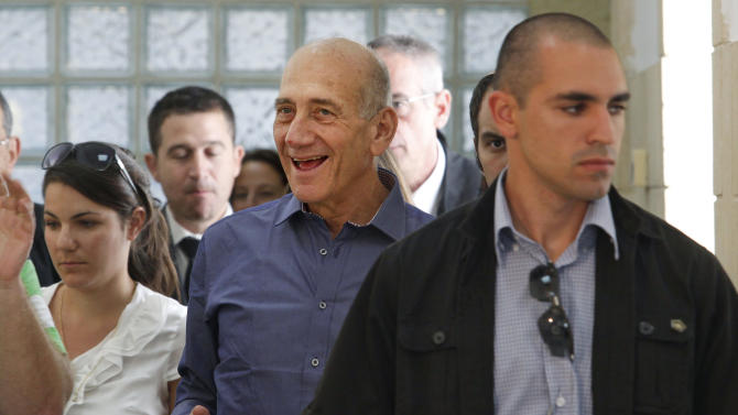 Former Israeli Prime Minister Ehud Olmert smiles at Jerusalem's District Court following a verdict hearing in his trial Tuesday, July 10, 2012. An Israeli court on Tuesday cleared Olmert of the major charges in a corruption trial that forced him from power. Olmert was found guilty of a lesser offense, and it was not clear whether that verdict could send him to jail. (AP Photo/Gali Tibbon, Pool)