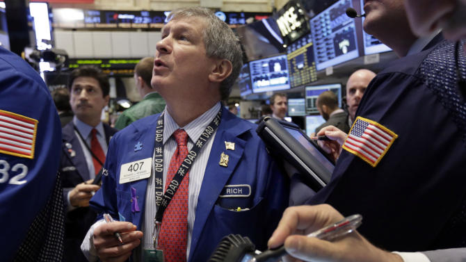 In this Thursday, Jan. 10, 2013, photo, Trader Richard Newman checks prices as he works on the floor of the New York Stock Exchange. Stocks edged lower on Wall Street, with the Standard & Poor's 500 slipping from close to a five-year high. Apple stocks tumbled on concern that demand for the iPhone 5 is waning.  (AP Photo/Richard Drew)