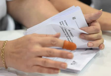 A woman counts ballots at a counting centre in Aberdeen